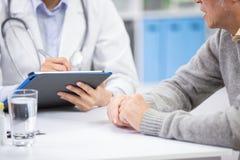 De vrouwelijke arts ziet oudere patiënt royalty-vrije stock fotografie