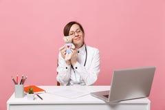 De vrouwelijke arts zit bij het bureauwerk aangaande computer met het medische die stuk speelgoed van de documentgreep in het zie stock afbeeldingen
