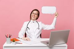De vrouwelijke arts zit bij het bureauwerk aangaande computer met de medische die wolk van de documentgreep in het ziekenhuis op  stock foto