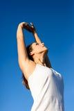 De vrouwelijke atleet het uitrekken zich wapens voor het uitoefenen en ontspannen Stock Afbeelding