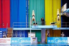 De vrouwelijke atleten presteren syncronized sprong Stock Afbeeldingen