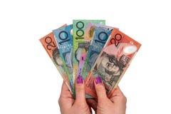 De vrouwelijke Australische die dollar van de handgreep op wit wordt geïsoleerd stock afbeelding