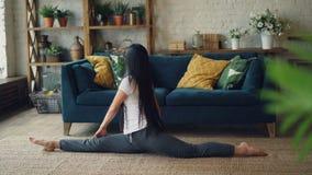 De vrouwelijke Aziatische turner leidt thuis het praktizeren op verdelend benen zittend op tapijt in woonkamer Actieve levensstij stock video