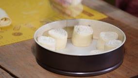 De vrouwelijke bakker zet broodjes aan bakselblad, omhoog sluit stock video