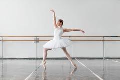 De vrouwelijke balletdanser houdt het rek in klasse stock foto