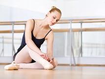 De vrouwelijke balletdanser rijgt de linten van pointes Stock Afbeeldingen