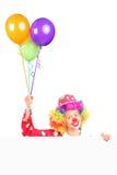 De vrouwelijke ballons van de clownholding achter een paneel Stock Foto's