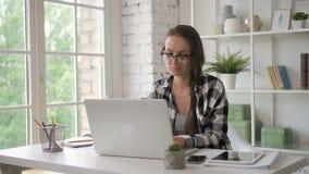 De vrouwelijke bedrijfseigenaaringenieur die werken aan investeert laptop in modern bureau saleswoman stock video