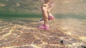 De vrouwelijke benen met roze manicured tenen onderwater lopen Standpunt van vrouw het lopen in zeewater bij zandig strand stock videobeelden