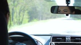 De vrouwelijke bestuurder achter wiel kijkt in autospiegel en ritten op weg in reis stock video