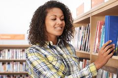 De vrouwelijke Bibliotheek van Studentenchoosing book in Royalty-vrije Stock Foto