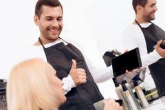 De vrouwelijke blije stilist kiest kapsel op tablet voor rijpe vrouw in schoonheidssalon stock afbeelding