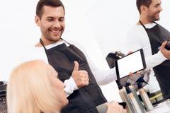 De vrouwelijke blije stilist kiest kapsel op tablet voor rijpe vrouw in schoonheidssalon royalty-vrije stock foto's