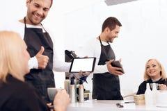 De vrouwelijke blije stilist kiest kapsel voor rijpe vrouw in schoonheidssalon stock afbeelding