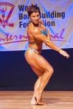 De vrouwelijke bodybuilder buigt haar spieren om haar lichaamsbouw te tonen Stock Foto
