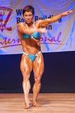 De vrouwelijke bodybuilder buigt haar spieren om haar lichaamsbouw te tonen Royalty-vrije Stock Afbeeldingen