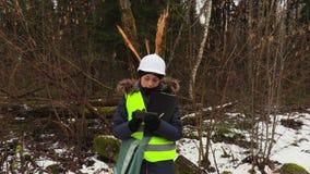 De vrouwelijke bosbouwwerknemer neemt beelden van gebroken boom stock video