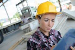De vrouwelijke bouwer schrijft in openlucht resultateninspectie Royalty-vrije Stock Foto