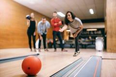 De vrouwelijke bowlingspeler werpt bal op steeg, stakingsschot stock foto