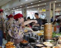 De vrouwelijke chef-kok brengt hete braadpan met hulpmiddel royalty-vrije stock afbeeldingen