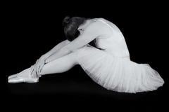 De vrouwelijke danser zit op vloer kijkend droevig in artistieke omzetting Stock Fotografie