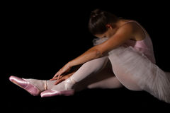 De vrouwelijke danser zit op vloer kijkend droevig in roze rustige tutu Stock Fotografie