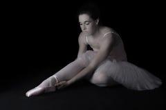 De vrouwelijke danser zit op vloer kijkend droevig in roze rustige tutu Royalty-vrije Stock Foto