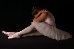 De vrouwelijke danser zit op vloer kijkend droevig in tutu Stock Fotografie