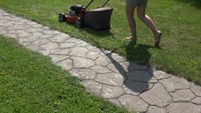 De vrouwelijke de duwmaaimachine van de tuinmanvrouw sneed gras dichtbij steen cobbled weg 4K stock videobeelden