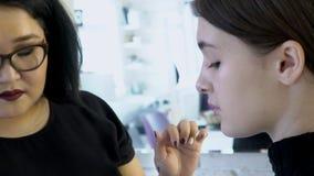 De vrouwelijke deskundige zet poeder binnen op vrouwengezicht in schoonheidsstudio stock footage