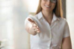 De vrouwelijke die hand voor handdruk, die tot samenwerking wordt uitgebreid bedriegt welkom heten stock foto