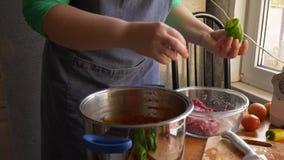 De vrouwelijke die kok in een schort met bereidt een paprika voor met vlees in keuken wordt gevuld Het meisje vult peper met geha stock videobeelden
