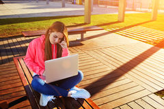 De vrouwelijke die student van het blondehaar en bezige gebruikende laptop computer bij campus wordt geconcentreerd Royalty-vrije Stock Foto's