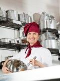 De vrouwelijke Draad van Chef-kokmixing egg with zwaait in Kom Stock Afbeeldingen