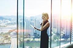 De vrouwelijke econoom bevindt zich dichtbij bureauvenster met mening van ontwikkeld bedrijfsdistrict in China royalty-vrije stock foto