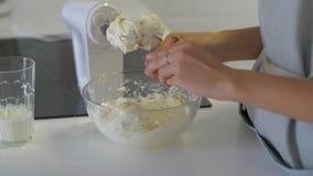 De vrouwelijke eieren van de handenonderbreking en gieten hen in een kom stock videobeelden
