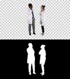 De vrouwelijke en mannelijke arts die het mobiele telefoons maken gebruiken roept het vertellen gelukkig nieuws, Alpha Channel stock afbeelding