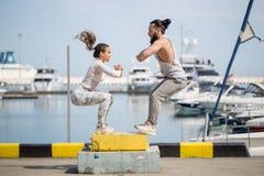De vrouwelijke en mannelijke atleet voert doossprongen uit openlucht royalty-vrije stock foto's