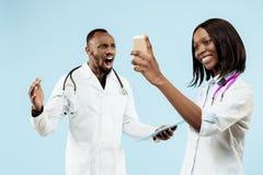 De vrouwelijke en mannelijke gelukkige afro Amerikaanse artsen op blauwe achtergrond royalty-vrije stock fotografie
