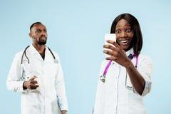 De vrouwelijke en mannelijke gelukkige afro Amerikaanse artsen op blauwe achtergrond stock afbeeldingen