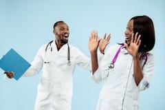 De vrouwelijke en mannelijke gelukkige afro Amerikaanse artsen op blauwe achtergrond stock afbeelding