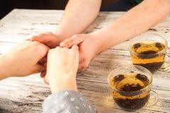 De vrouwelijke en mannelijke handen worden gehouden op de lijst Handen en thee op weefsel achtergrondexemplaarruimte en close-up stock afbeelding