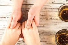 De vrouwelijke en mannelijke handen worden gehouden op de lijst Handen en thee op weefsel achtergrondexemplaarruimte en close-up stock fotografie
