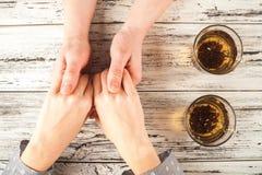De vrouwelijke en mannelijke handen worden gehouden op de lijst Handen en thee op weefsel achtergrondexemplaarruimte en close-up royalty-vrije stock foto