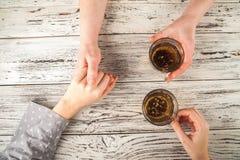 De vrouwelijke en mannelijke handen worden gehouden op de lijst Handen en thee op weefsel achtergrondexemplaarruimte en close-up royalty-vrije stock afbeeldingen
