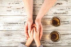 De vrouwelijke en mannelijke handen worden gehouden op de lijst Handen en thee op weefsel achtergrondexemplaarruimte en close-up royalty-vrije stock afbeelding