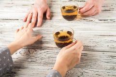 De vrouwelijke en mannelijke handen worden gehouden op de lijst Handen en thee op weefsel achtergrondexemplaarruimte en close-up stock foto