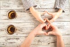 De vrouwelijke en mannelijke handen worden gehouden op de lijst Handen en thee op weefsel achtergrondexemplaarruimte en close-up stock foto's