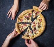 De vrouwelijke en mannelijke Pizza Carbonara van de handenbesnoeiing op zwarte steenachtergrond Italiaanse Pizza Carbonara met Ba Stock Foto's