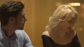 De vrouwelijke en mannelijke vreemdelingen die bij barlijst zitten, het ruilen kijkt op Vrijdag nacht stock video